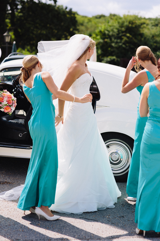 Bridesmaids helping Bride getting into the Rolls Royce