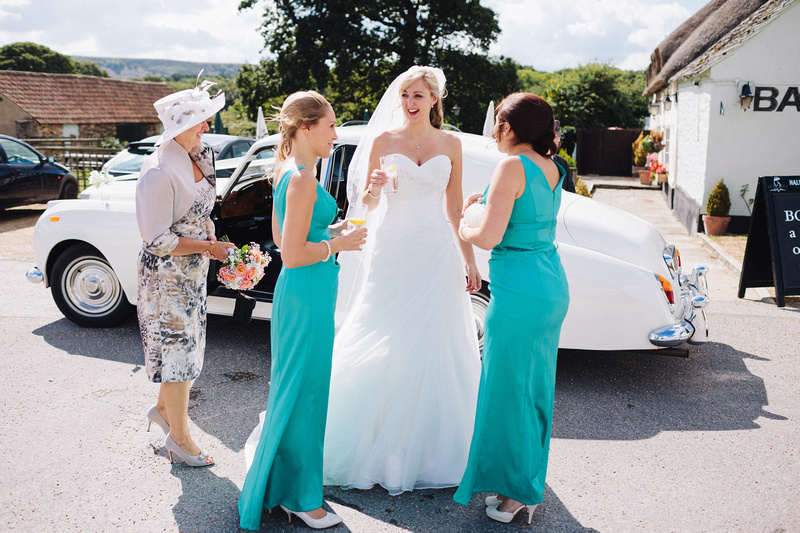 Bride with bridesmaids having a drink outside near the wedding car