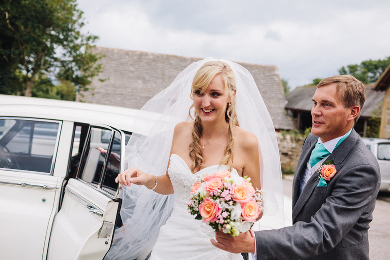 Smiling Bride in Dorset getting out of her Wedding Transport
