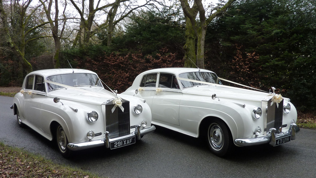 Two White Classic Rolls-Royce Silver Cloud standing side by side with Ribbons